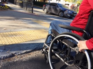 Wheelchair user at curb ramp that isn't flush with road