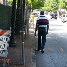 Closed sidewalk forces man to walk in the road