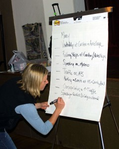 Volunteer writing on flip chart at public meeting