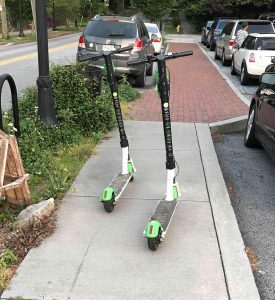 2 e-scooters parked on narrow sidewalk