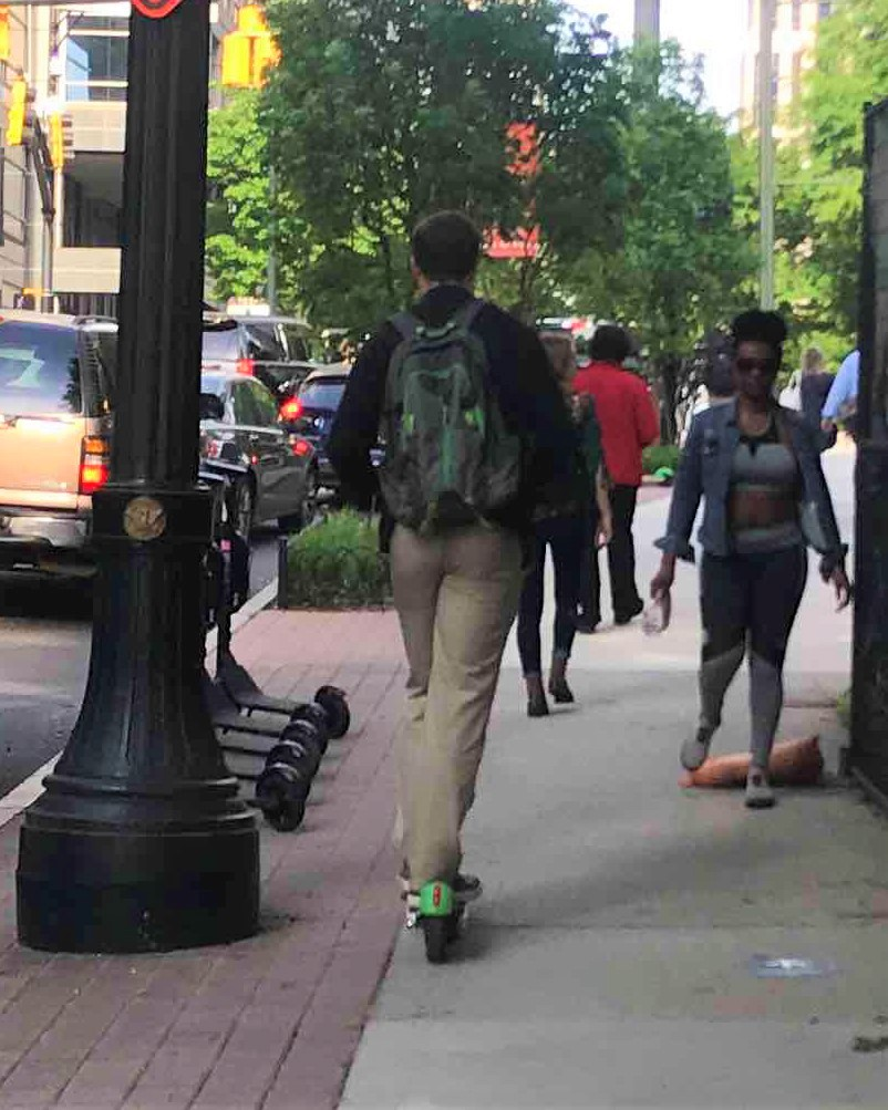 Man riding scooter on crowded sidewalk